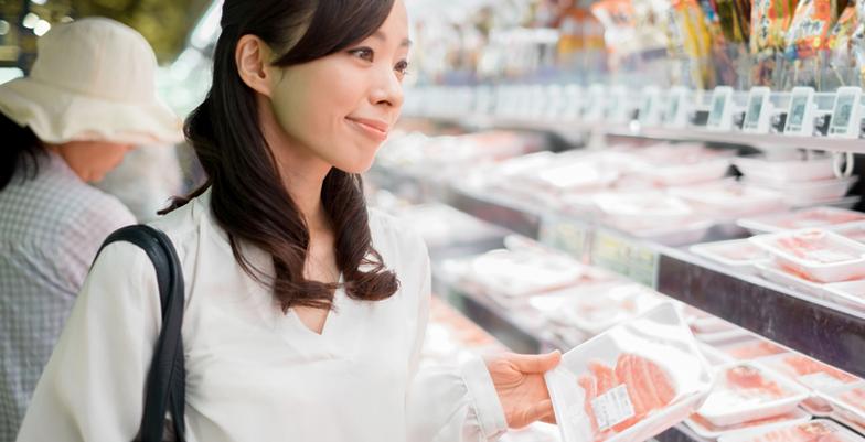 店頭でお肉を買う女性